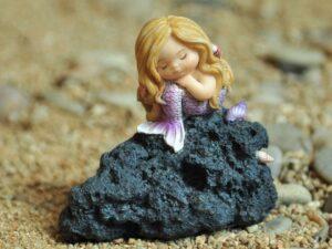 Tankefuld havfrue på klippe